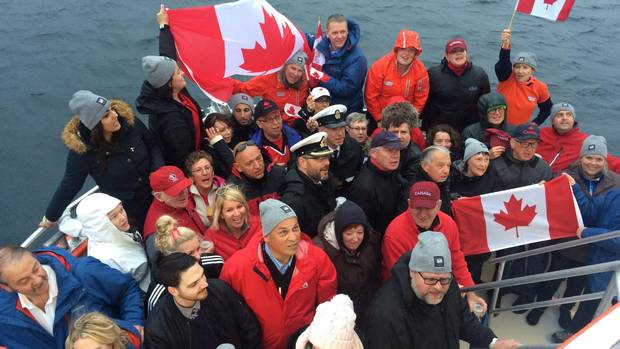 People take part in an Iceberg Quest sunrise tour off the coast of Cape Spear, N.L. on Saturday, July 1, 2017. Rain and low clouds blocked the sunrise over the flashing lighthouse at Cape Spear but that didn't bother the flag-waving crowd.