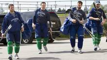 Vancouver Canucks, from left, Jeff Tambellini, Victor Oreskovich, Chris Higgins and Maxim Lapierre arrive for a team practice at the UBC Thunderbird Arena in Vancouver, B.C., Tuesday. (JONATHAN HAYWARD/The Canadian Press)