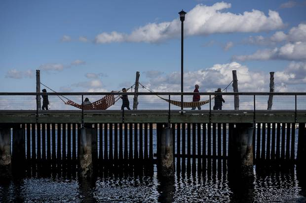 Pedestrians walk past hammocks on the Halifax waterfront.