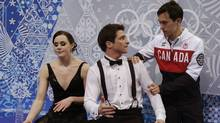 """Tessa Virtue and Scott Moir of Canada react with teammate Patrick Chan, right, in the """"kiss and cry"""" area during the Team Ice Dance Short Dance at the Sochi 2014 Winter Olympics on Feb. 8. (Darron Cummings/Reuters)"""