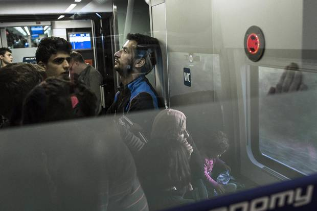 Says Basel Omran, centre, seen here on a train bound for Munich: 'I would hold all the happiness in the world in my hands if my family were here.'