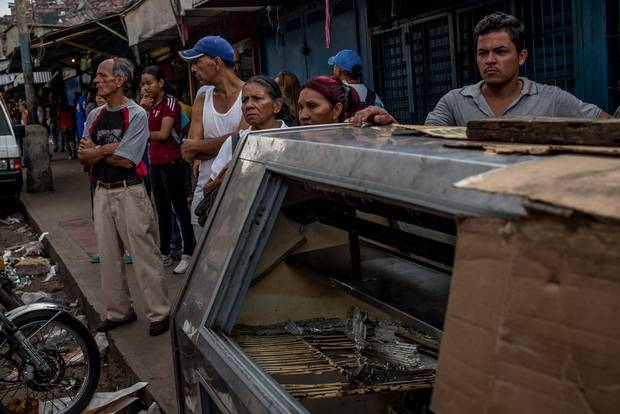 People gather on the street in the El Valle neighbourhood of Caracas after a night of looting in the area saw eight people die.
