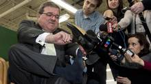 Finance Minister Jim Flaherty puts on his annual pre-budget shoes at the Roots Leather Factory in Toronto on March 20, 2013. (NATHAN DENETTE/THE CANADIAN PRESS)