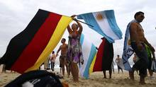 A woman waves German and Argentine flags on Copacabana beach ahead of Sunday's World Cup final match between Argentina and Germany in Rio de Janeiro July 11, 2014. (Reuters)