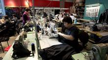 Workers assemble Lululemon pants at a factory in Vancouver. Lululemon has beaten analyst forecasts for 24 quarters in a row. (Jonathan Hayward/The Canadian Press)