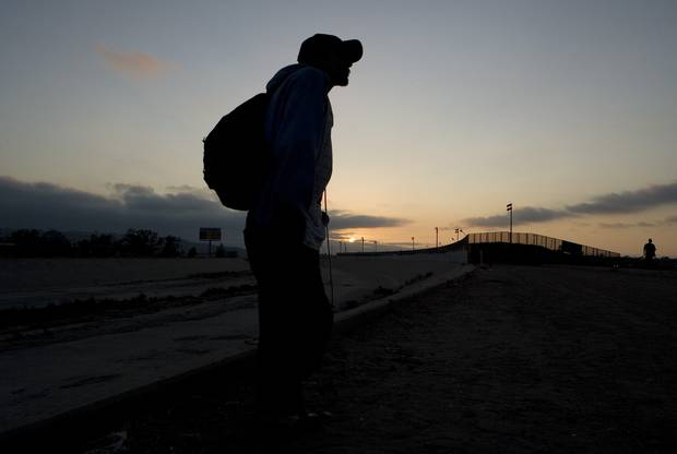 A man planning to cross into the U.S. illegally stands near the dry concrete-lined Tijuana River basin, on the Mexican side of the U.S.-Mexico border in 2008.