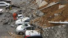 Vehicles are crushed by a collapsed wall at a car park in Mito city, Japan. (JIJI PRESS/Jiji Press/AFP/Getty Images)