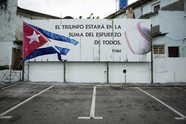 "The stadium where the Industriales team plays features a quote attributed to Fidel Castro: ""Victory will be in the sum of efforts of all,"" in Havana, Dec. 20, 2014. Whether in organized games on diamonds with frayed backdrops or in pickup games in the street, baseball is still very much a part of Cuba's people."
