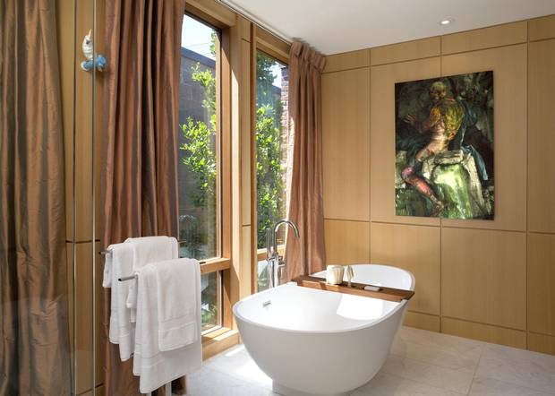 The master bathroom features floor-to-ceiling windows next to the tub.