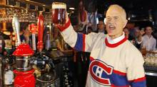 NDP Leader Jack Layton raises a pint during a campaign stop at a sports bar in Montreal during the Habs-Bruins playoff game on April 14, 2011. (SHAUN BEST/REUTERS)