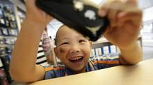 A 5-year-old boy plays games on an iPhone in the company's flagship store in Beijing's Sanlitun Area, which is one of four official Apple stores in China, July 22, 2011. (JASON LEE/Jason Lee/Reuters)