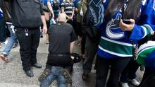 Security arrest a spectator while Vancouver Canucks fans prepare to watch first period Stanley Cup final game 5 action against the Boston Bruins in downtown Vancouver, Friday, June 10, 2011. (Geoff Howe/ The Canadian Press/Geoff Howe/ The Canadian Press)