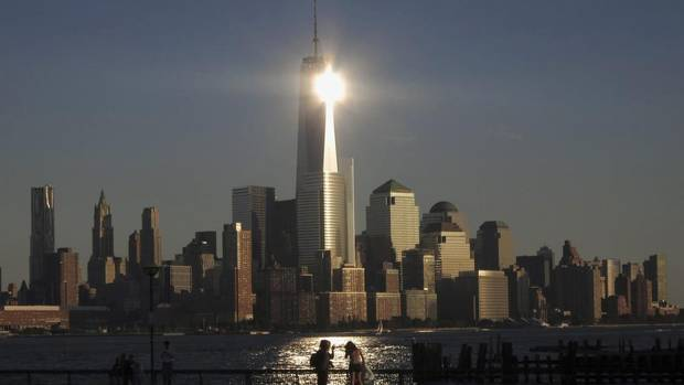 The sun reflects off New York's One World Trade Center as people stand in a park in Hoboken, N.J. The building, at 1,776 feet with the spire included, is now the tallest building in the United States. (GARY HERSHORN/REUTERS)