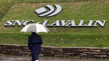 A pedestrian walks past the SNC-Lavalin Group Inc., headquarters in Montreal. (© Christinne Muschi / Reuters/REUTERS)