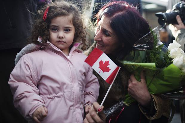 Newly arrived Syrian refugee Elo Manushian, right, is united with her granddaughter Rita Mahserjian, left, in Toronto on Dec. 11, 2015.