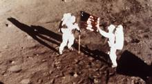 "In this July 20, 1969 file photo provided by NASA shows Apollo 11 astronauts Neil Armstrong and Edwin E. ""Buzz"" Aldrin, the first men to land on the moon, plant the U.S. flag on the lunar surface. (NASA/AP)"
