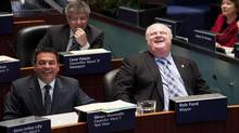 "Toronto Mayor Rob Ford, right, laughs after councillor Giorgio Mammoliti, left, jokingly states ""I'm only doing what the mayor wants me to do"" during a council meeting to discuss the city's 2013 proposed budget debate in Toronto on Jan. 15, 2013. (Michelle Siu For The Globe and Mail)"