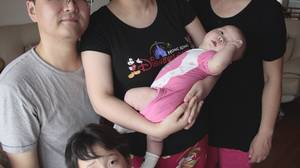 Frank Zhou and his wife Grace Li took advantage of a loophole in China's one-child policy in order to have a sister for their daugher, Zhou Zhixuan, who is 5. Grandmother Chen Yili, right, helps care for the two-month old baby, Zhou Zhining.