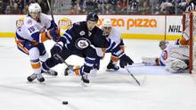 Winnipeg Jets' Alexander Burmistrov and New York Islanders' P.A. Parenteau fight for the puck in front of goaltender Evgeni Nabokov in Winnipeg, Feb. 14, 2012. (Fred Greenslade/Reuters/Fred Greenslade/Reuters)