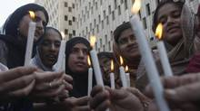 Women light candles while taking part in a rally to commemorate International Women's Day in Karachi on March 8, 2013. (ATHAR HUSSAIN/REUTERS)