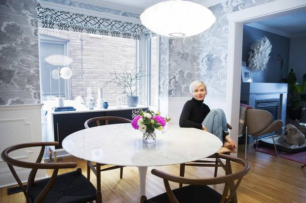 Emilia Wisniewski poses for a photo in her dining room which features Fornasetti Nuvolette wallpaper, a George Nelson saucer crisscross pendant lamp, a Saarinen Marble Tulip Table and Hans J Wegner Wishbone chairs in Toronto on January 9, 2018.