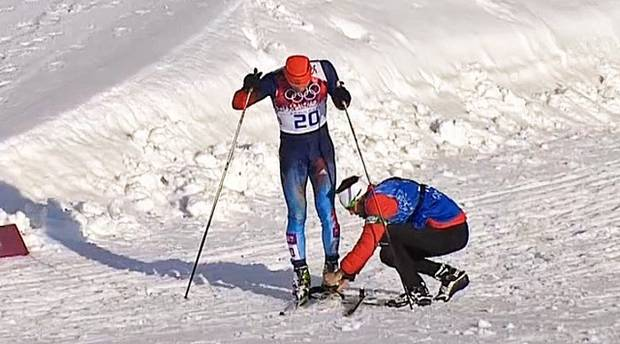 Justin Wadsworth, head coach of the Canadian ski team, lends a hand to Russian Anton Gafarov who had fallen and broken one of his skis at the Sochi Olympic Games on February 11, 2014.