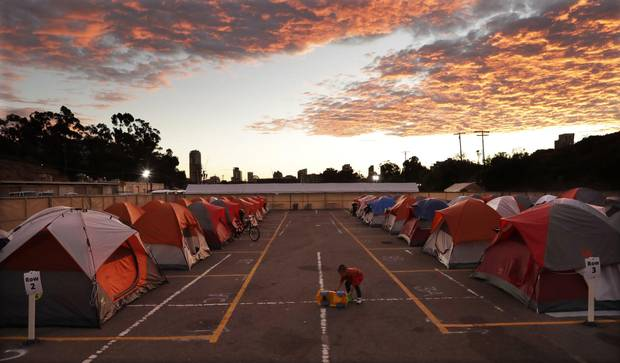 A boy plays as the sun sets over donated tents for homeless families lined up on a parking lot in the city-sanctioned encampment in San Diego in November, 2017. Scores of tents, mobile medical units, portable toilets and showers were brought in to meet the needs of hundreds of homeless people.