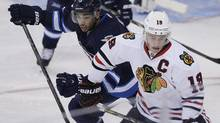 Winnipeg Jets' Evander Kane (9) and Chicago Blackhawks' Jonathan Toews (19) jostle for position during third period NHL action in Winnipeg on Saturday, November 2, 2013. (JOHN WOODS/THE CANADIAN PRESS)