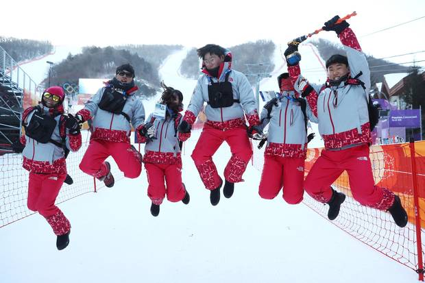 Volunteers pose for a photo after the Ladies' Giant Slalom was postponed due to strong winds on day three at the Pyeongchang Winter Games.