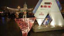 A gay rights activist stands with a banner near the Olympic countdown clock in front of the Kazan Cathedral in Central St. Petersburg February 5, 2014. With the Winter Olympics only two days away, campaigners have urged major corporate sponsors to speak out about the way Games host Russia treats gay people. (Maxim Zmeyev/REUTERS)