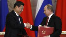 Russia's President Vladimir Putin exchanges documents with his Chinese counterpart Xi Jinping during a signing ceremony at the Kremlin in Moscow March 22, 2013. (SERGEI KARPUKHIN/REUTERS)