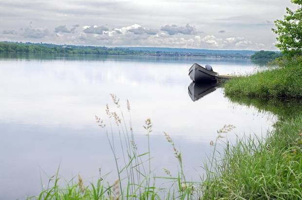 A motor boat sits tied up to a dock along the Saint John River in New Brunswick.