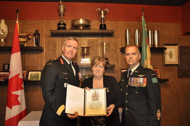 Brigadier-General Stephen Cadden, left, commander of 4th Canadian Division, and Chief Warrant Officer Stuart Hartnell presented the Memorial Cross and Sacrifice Medal to Corporal John Unrau's mother, Dorothy, on Oct. 26 at the Sudbury Armoury. Cpl. Unrau, an Afghanistan war veteran, died by suicide on Canada Day in 2015.