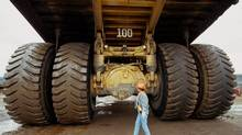 A Syncrude heavy equipment opperator is dwarfed by the rear tires of the Caterpillar 797 dump truck as she completes her pre-shift walk-around. (John Ulan/The Globe and Mail)