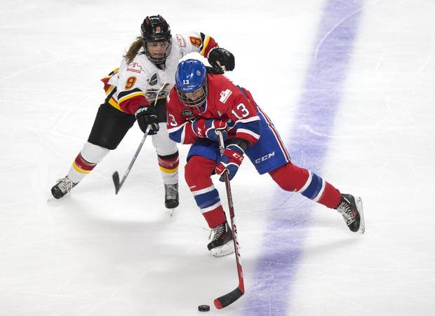Les Canadiennes Caroline Ouellette battles Calgary Inferno's Sarah Davis for the puck during their Canadian Women's Hockey League game in Montreal, Dec. 10, 2016.