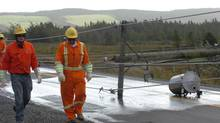 Newfoundland Power employees walk past fallen power poles on Ruby Line near St. John's N.F. on Tuesday, Sept. 11, 2012 after power was cut to the area. (Keith Gosse/THE CANADIAN PRESS)