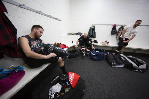 Members of the Calgary Pioneers hockey team get dressed before their game in Calgary on Dec. 3, 2016.