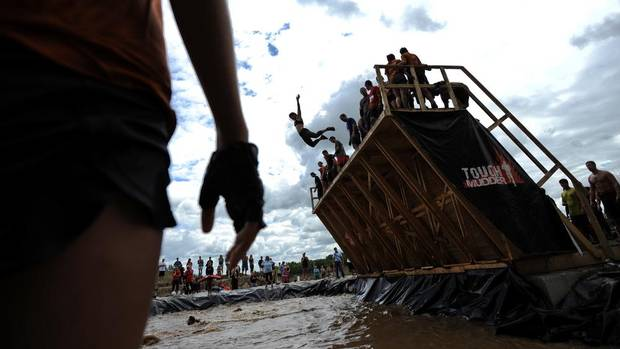 A participant leaps off a platform in an obstacle called Walk the Plank. Over 15,000 people signed up for the Mount St. Louis Tough Mudder, a military-style obstacle course designed to test participants' endurance, strength and heart, August 18, 2012. (Galit Rodan/The Globe and Mail)