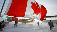 A Canadian flag flies from a snowmobile as military personnel gather during a Canadian Ranger sovereignty patrol in Eureka, on Ellesmere Island, Nunavut, Saturday, Mar. 31, 2007. (Jeff McIntosh/The Canadian Press/Jeff McIntosh/The Canadian Press)