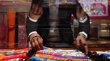 A saleswoman arranges scarves inside a Hermes showroom in Mumbai August 23, 2011. (DANISH SIDDIQUI/REUTERS)