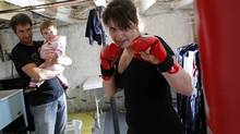 Dr. Ryan Rhodes says that partner support is key in keeping fit post-pregnancy. Here, Jodi Di Menna kickboxes in her basement while her husband takes on kid-sitting duties. (Blair Gable/© 2009, Blair Gable Photography)