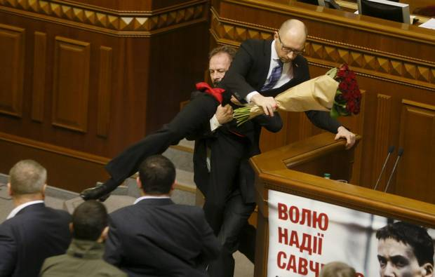 A deputy from Ukrainian President Petro Poroshenko's political party attacks Ukrainian Prime Minister Arseniy Yatsenyuk after presenting him with a bouquet of roses during the annual report of the government in the Ukrainian parliament in December 2015. The political crisis between president and prime minister is ongoing.