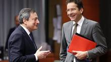 European Central Bank (ECB) President Mario Draghi talks to Dutch Finance Minister and Eurogroup chairman Jeroen Dijsselbloem (right) during a euro zone finance ministers meeting in Brussels December 17, 2013. (Francois Lenoir/Reuters)