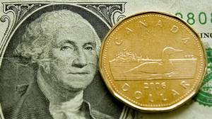 A Canadian dollar, or loonie, sits on its American counterpart