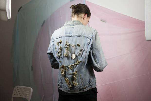 Mx. Gilmer-Osborne wears a denim jacket decorated with their parents' and their own trophies. 'I removed the trophy heads and attached them to my oldest denim jacket … my way of carrying my parents with me at all times, while also enjoying the process of destroying symbols of triumph/success/physical ability in order to display them in a queer manner.'