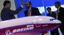 Visitors talk next to a Boeing 777X aircraft model at the Singapore Airshow Feb. 13, 2014. (Edgar Su/Reuters)