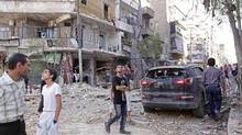 Civilians look at the sky as they inspect the damage in the area after an air strike at Al-Shaar neighbourhood in Aleppo, Syria. (Zain Karam/Reuters)