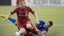 Toronto FC Richard Eckersley left, and Montreal Impact Felipe Martins right tangle as they battle for possession of the ball during first half MLS action at the Olympic Stadium in Montreal on Saturday March 16, 2013. (Peter McCabe/THE CANADIAN PRESS)
