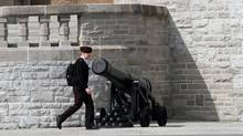 A cadet from the Royal Military College of Canada walks by a canon near the Parade square at the campus of RMC in Kingston, Ontario on Monday April 8, 2013 (Lars Hagberg for The Globe and Mail)