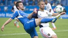 Montreal Impact's Jeb Brovsky, left, tackles Real Salt Lake's Chris Wingert during first half MLS soccer action in Montreal, Saturday, May 11, 2013. (The Canadian Press)